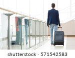 young man pulling suitcase in... | Shutterstock . vector #571542583