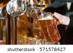 beer is poured into a glass | Shutterstock . vector #571578427