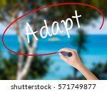 Small photo of Woman Hand Writing Adapt with black marker on visual screen. Isolated on nature. Business concept. Stock Photo