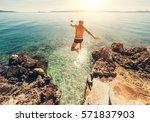 man jumps in blue sea lagoon... | Shutterstock . vector #571837903