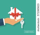 gift home. man holding a white... | Shutterstock .eps vector #572385823