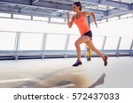 young woman sprinting on... | Shutterstock . vector #572437033