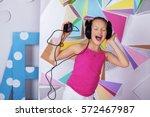 funny child girl in headphones... | Shutterstock . vector #572467987