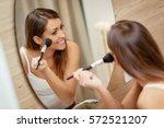 beautiful young woman applying... | Shutterstock . vector #572521207