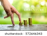 Small photo of DEBENTURE word and hand walking on a pile of coins with blurry background.