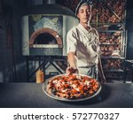 young male cook holding... | Shutterstock . vector #572770327