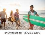friends carrying a surfboard... | Shutterstock . vector #572881393