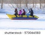 Small photo of Pavlodar, Kazakhstan - January 15, 2017: Passengers on a towable tube on the frozen river side view