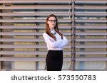 Small photo of Ambitious modern young women woman, business woman, student posing for camera, smiling, change posture, arms crossed in front of him standing on background of large gray window of business center