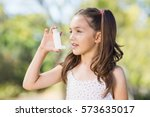 Small photo of Girl using an asthma inhaler in the park