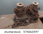 Small photo of Old Knecht: steam cabinet with common ground on the docks of metal rusty brown burgundy, on the cabinet metal heavy chain to bind the ships on a background of the river.