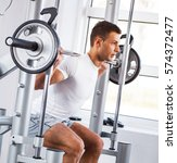man doing squats on squatting... | Shutterstock . vector #574372477