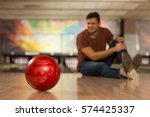 Small photo of He hurt his knee. Young man sitting on the floor at the bowling club holding his injured knee after playing bowling selective focus on the bowling ball copyspace sports injury pain hurting concept