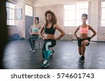 Small photo of Portrait of young women exercising in aerobics class. Three females doing workout together in gym.