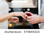 man putting engagement ring on... | Shutterstock . vector #574844323