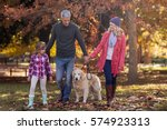 Stock photo family walking with dog at park during autumn 574923313