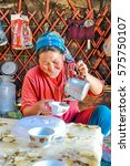 Small photo of Ala Archa, Kyrgyzstan - circa September 2011: Smiling native woman dressed in red t-shirt and with headcloth on her head pours tea into cup in Ala Archa, Kyrgyzstan. Documentary editorial.