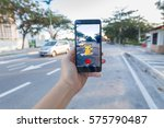 Small photo of Penang, Malaysia - August 13, 2016 : Man holding a smartphone with his left hand playing Pokemon Go game.