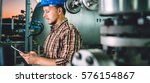 man wearing blue hardhat using... | Shutterstock . vector #576154867