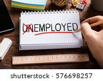 Small photo of High Angle View Of Person Hand Changing Unemployed To Employed On Notepad. Job And Employment Concept