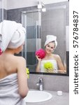 Small photo of Beauty yang smiling girl with pink and yellow wisp in white towels in grey bathroom after shower looking in the mirror