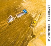 Small photo of Aerial view of a working bulldozer and truck ion a construction site. Industrial background and heavy industry from above.