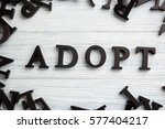 Small photo of Word ADOPT on light wooden background