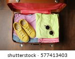 open suitcase with clothes on... | Shutterstock . vector #577413403