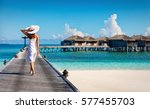 Small photo of Woman in white walking over a wooden jetty in the Maldives