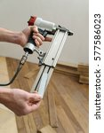 Small photo of Installing a wooden floor. A worker is charging nails in air gun.