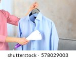 woman ironing shirt with... | Shutterstock . vector #578029003