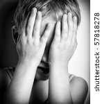 BW portrait of sad crying little boy covers his face with hands - stock photo