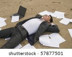 young guy in a business suit is on the beach among the scattered papers - stock photo