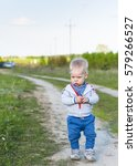 Small photo of A small, alone, sad, alone year old child, a boy, walks on the path in the countryside on a sunny day, keeps little stones in heands