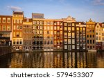 Stock photo traditional old buildings and boats at sunset in amsterdam netherlands 579453307
