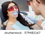Small photo of Dental fillings. Close up of a beautiful senior female patient getting dental fillings fixed with ultraviolet lamp professionalism technology modern equipment UV healthcare filling dentistry medical