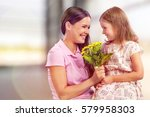 woman and child with bouquet of ... | Shutterstock . vector #579958303