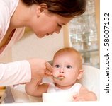 mum spoon feeds the child in... | Shutterstock . vector #58007152