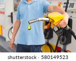 man hold fuel nozzle to add... | Shutterstock . vector #580149523