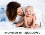 mother and child on a white bed.... | Shutterstock . vector #580300963