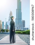 Small photo of Confident Arab employee. Arab Business vumen in hijab is the street on the background of skyscrapers of Dubai. The woman is dressed in a black abaya