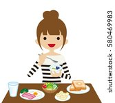 young woman eating breakfast | Shutterstock .eps vector #580469983