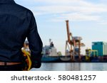 Small photo of Hand's engineer worker holding yellow safety helmet with blurred Shipping port