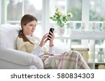 young woman using smartphone  | Shutterstock . vector #580834303