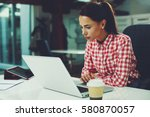young woman working on laptop... | Shutterstock . vector #580870057