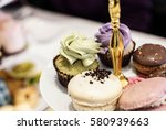 Small photo of traditional afternoon high tea in hotel with Macaroons and cupcake sweets