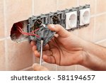 Small photo of Electrician hands tighten electrical wires in wall fixture or socket using a screw driver - closeup