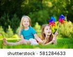 two cute little girls holding... | Shutterstock . vector #581284633
