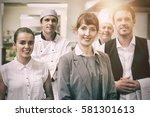 Small photo of Portrait of young female manager posing in modern kitchen with staff