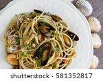 Small photo of Spaghetti allo scoglio, pasta with seafood in white ceramic plate on wooden background